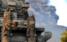 Mount Agung's eruption is seen next to a Balinese temple at Kubu sub-district in Karangasem Regency on Indonesia's resort island of Bali on 26 November 2017. Picture: AFP.