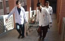 Pakistani paramedics transport an injured bomb blast victim to a hospital after the bombing at a market in Kohat on 23 November 2018. Picture: AFP