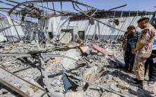 Military officers of the Libyan Government of National Accord (GNA)inspect damage and debris at a migrant detention centre used by the GNA in the capital Tripoli's southern suburb of Tajoura on July 3, 2019, following an air strike on a nearby building that left dozens killed the previous night. Picture: AFP.