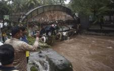 Onlookers and residents take photos of a car washed away by flash floods following heavy overnight rains in Pune on September 26, 2019. Picture: AFP.