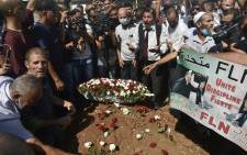 Algerians place roses on the tomb of former president Abdelaziz Bouteflika during his funeral at the El-Alia cemetery in the capital Algiers on September 19, 2021. Picture: Ryad Kramdi / AFP.