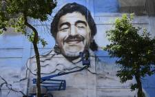 Argentine street artist Alfredo Segatori controls an elevator he uses to paint a mural of late Argentine football legend Diego Maradona in Buenos Aires, on December 1, 2020. Picture: AFP