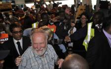 Professor Cyril Karabus is surrounded by supporters at Cape Town International Airport, shortly after his arrival. Picture: Department of International Relations.