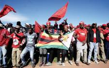 Zimbabwe main opposition party Movement for Democratic Change Alliance (MDC) supporters hold MDC and Zimbabwe flags as they gather to listen to their leader Nelson Chamisa during an election campaign rally on 21 July 2018 at White City stadium in Bulawayo. Picture: AFP.
