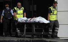 The body of a man who tried to attack a police station is carried out of the premises in Cornella near the northeastern Spanish city of Barcelona on 20 August 2018. Picture: AFP.