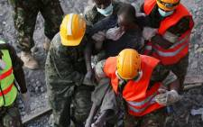 FILE: Rescue workers carry a survivor from the rubble of an apartment block, which collapsed six days previously, on 5 May 2016 in Nairobi. Picture: AFP.