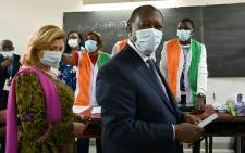 FILE: Ivorian President Alassane Ouattara (2nd R) and his wife Dominique Ouattara (L) arrives to vote at a polling station in Abidjan on 31 October 2020, during Ivory Coast's presidential election. Picture: AFP.