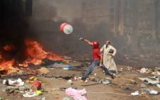 A supporter of the Muslim Brotherhood and Egypt's ousted president Mohamed Morsi throws a water container onto a fire during clashes with police in Cairo on 14 August 2013. Picture: AFP