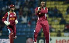 West Indies cricketer Chris Gayle (R) celebrates the wicket of England cricketer Jonathan Bairstow with wicket keeper Denesh Ramdin during the ICC Twenty20 Cricket World Cup's Super Eight match between England and West Indies at the Pallekele International Cricket Stadium in Pallekele on September 27, 2012. Picture: AFP.