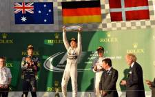 Mercedes driver Nico Rosberg of Germany (C) holds up his award in celebration next to second-placed Red Bull driver Daniel Ricciardo of Australia (L) and third-placed McLaren driver Kevin Magnussen of Denmark (R) on the podium after the Formula One Australian Grand Prix in Melbourne on March 16, 2014. Picture: AFP.