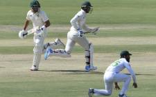 South Africa's Aiden Markram (L) and Rassie van der Dussen (C) run between the wickets as Paistan's Fawad Alam watches during the third day of the first cricket Test match between Pakistan and South Africa at the National Stadium in Karachi on 28 January 2021. Picture: Asif Hassan/AFP