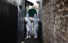 Health workers remove the body of a man who died of COVID-19 coronavirus at his Home in Bandung on June 23, 2021, as Indonesia's infection rates soar and hospitals are flooded with new patients, prompting warnings that the Southeast Asian nation's health crisis could spiral out of control. Picture: AFP.