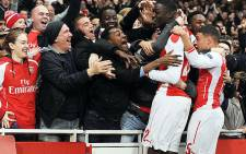 Arsenal fans celebrate with Yaya Sanogo and Alex Oxlade-Chamberlain after reaching the last 16 of the Uefa Champions League on 26 November 2014. Picture: Arsenal Facebook page.