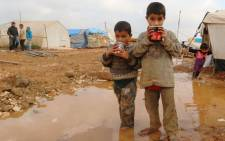FILE: Displaced Syrian children stand in muddy water after heavy rains in the Bab Al-Salama. Picture: AFP