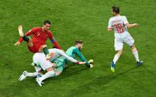 Portugal's forward Cristiano Ronaldo (L) falls down next to de Spain's goalkeeper David De Gea (C) during the Russia 2018 World Cup Group B football match between Portugal and Spain at the Fisht Stadium in Sochi on 15 June, 2018. Picture: AFP.