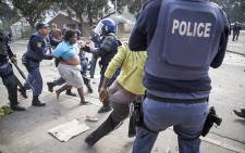 FILE: After issuing a warning order for a crowd of roughly 400 people in Masiphumelele township in Cape Town, police began arresting protesting residents. Some fell over in the scramble, their clothing coming off in the chaos. Picture: Thomas Holder/EWN.