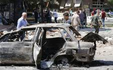 FILE: Syrian men stand next to a charred vehicle as they inspect the damage at the site of a suicide bomb attack in the capital Damascus' eastern Tahrir Square district, on July 2, 2017. Picture: AFP.