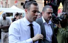 Oscar Pistorius is escorted into the High Court in Pretoria ahead of day 21 of his murder trial. Picture: Sebabatso Mosamo/EWN