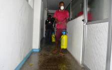 An employee disinfects an office in Monrovia where offices were closed for disinfection against the epidemic of the haemorrhagic fever Ebola on 1 August 2014. Picture: AFP.