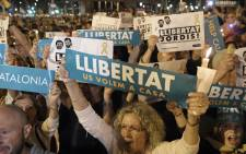 FILE: People hold placards reading 'Freedom' during candle-lit demonstration in Barcelona against the arrest of two Catalan separatist leaders on 17 October 2017. Picture: AFP