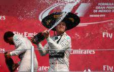 Nico Rosberg of Germany and Mercedes GP celebrates on the podium next to Lewis Hamilton of Great Britain and Mercedes GP after winning the Formula One Grand Prix of Mexico at Autodromo Hermanos Rodriguez on 1 November, 2015 in Mexico City, Mexico. Picture: AFP.