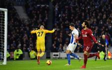Liverpool's Egyptian midfielder Mohamed Salah (R) celebrates after scoring the opening goal from the penalty spot during the English Premier League football match between Brighton and Hove Albion and Liverpool at the American Express Community Stadium in Brighton, southern England on 12 January 2019. Picture: AFP