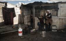 FILE: Linda Avontuur, stands with four of her five children, with most of their possessions, packed out in front of the shack in which they live, in Egoli Informal Settlement, close to Strandfontein, on 2 April 2014, Cape Town. Picture: AFP.