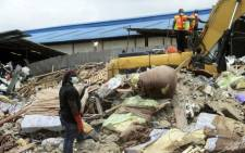 Rescue workers clear away mattresses used by occupants of the collapsed guesthouse of the Synagogue Church of All Nations at Ikotun in Lagos on 17 September, 2014. Picture: AFP.