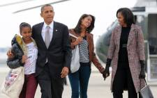 """US President Barack Obama, First Lady Michelle Obama and their daughters Mali and Shasa borad Air Force One at Chicago O'Hare International Airport in Chicago on November 7, 2012. Obama returns to Washington on Wednesday emboldened by his re-election but facing the daunting task of breaking down partisan gridlock in a bitterly divided Congress. Obama told Americans """"the best is yet to come"""" after defying dark economic omens to handily defeat Mitt Romney, but his in-tray is already overflowing with unfulfilled first term wishes thwarted by blanket Republican opposition. Picture: AFP."""