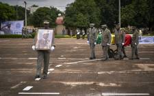A Mali military officer (L) carries a portrait of former Mali President Moussa Traore while Military pallbearers carry his coffin draped with the Mali national flag during his funeral in Bamako on September 18, 2020.  Picture: AFP