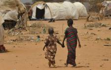 This file photo taken on 10 July, 2011 shows newly arrived Somali refugees walking to a registration center at the Daadab refugee camp on 10 July, 2011 in northeastern Kenya. Picture: AFP.