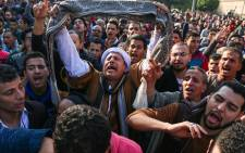 Egyptians shout slogans as they gather outside the Saint Peter and Saint Paul Coptic Orthodox Church in Cairo's Abbasiya neighbourhood after it was targeted by a bomb explosion on 11 December, 2016. Picture: AFP.