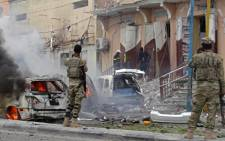 FILE: Somalian security personnel look towards burning vehicles as they secure an area in Mogadishu on 30 July 2017 after a car bomb explosion in the Somalian capital. Picture: AFP.