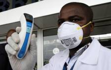 An agent of the national public health institute poses with a thermometer at the airport, in Abidjan on 12 August, 2014. Picture: AFP.