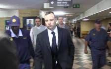 Oscar Pistorius is escorted into the High Court in Pretoria ahead of his murder trial on 14 April 2014. Picture: Reinart Toerien/EWN.
