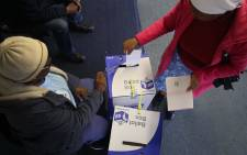 FIlE: A voter placing her marked ballots into the local and national ballot boxes on 8 May 2019. Picture: EWN