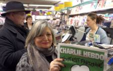 A woman displays the latest edition of French satirical magazine Charlie Hebdo shortly after it went on sale on January 14, 2015 in Marseille. The first issue of the magazine to be published since a jihadist attack decimated its editorial staff last week was sold out within minutes at kiosks across France. Picture: AFP.