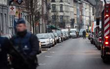 Belgian police officers stand guard in a street during a police action in the Molenbeek-Saint-Jean district in Brussels, on 18 March 2016. Picture: AFP.