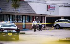 Law enforcement officers are seen outside a billiard club that was rented for a concert, after three gunmen killed two people and injured at least 20 people overnight in the Hialeah area of Miami Dade county on May 30 2021. Picture: AFP.