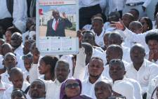 A man holds a calender with the portrait of late Burundi President Pierre Nkurunziza, who died at the age of 55, as people wear white clothes while attending the national funeral at the Ingoma stadium in Gitega, Burundi, on 26 June 2020. Picture: AFP