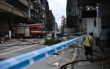 A fireman (C) is seen next to a fire truck in a cordoned off residential area in Macau on 24 August 2017, a day after Typhoon Hato hit the city. Picture: AFP