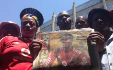 Soccer fans hold a poster of slain Orlando Pirates and Bafana Bafana captain Senzo Meyiwa ahead of a combined memorial service at the Standard Bank Arena in Johannesburg on 30 October 2014. Picture: Reinart Toerien/EWN.