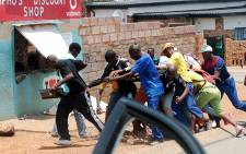 A group of looters break into a foreign-owned store in White City, Soweto on 22 January 2014. Picture: SA Crime Fighters via Twitter