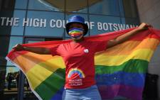 Activists carry a rainbow flag outside the Botswana High Court on 12 October 2021 where they gathered to listen to the court proceedings as the goverment of Botswana appeals against the Botswana High Court ruling to decriminalise homosexuality. Picture: Monirul Bhuiyan/AFP