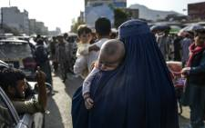A woman cradling a baby in her arms walks through a market area in Kabul. Picture: AFP