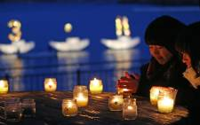 """Residents pray for the quake and tsunami victims before candle lights while a candle boat displays """"3.11"""" letters in Kamaishi, Iwate prefecture on 11 March, 2016."""