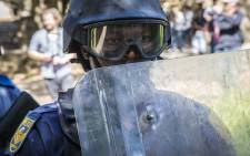 FILE: A Saps member walks close to his shield during sporadic running battles between police and #FeesMustFall supporters at Wits University on 11 October 2016. Picture: Reinart Toerien/EWN