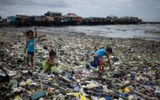 Children collect plastic water bottles among the garbage washed ashore as a result of a storm surge of typhoon Haima at the Manila Bay on 20 October 2016. Picture: AFP.