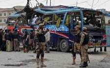 Pakistani security officials inspect a damaged bus after a bomb blast in Peshawar on 16 March, 2016. Picture: AFP.