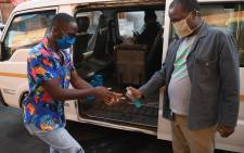 FILE: A man receives hand sanitiser as a preventive measure against the spread of the COVID-19 coronavirus before boarding a taxi in Gaborone on 21 May 2020. Botswana President Mokgweetsi Masisi ended the 48-day national lockdown on 21 May 2020 but kept some restrictions, including movement between regions. Picture: AFP